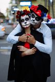 A couple, wearing skull make-up for. All souls day. Boy and girl sugar skull makeup.painted for halloween standing on the street. royalty free stock photography