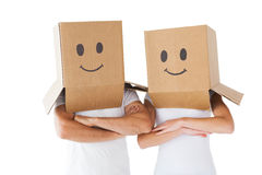 Couple wearing smiley face boxes on their heads Stock Photos