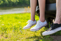Couple Wearing Sneakers Sitting on Tailgate of Car. Close Up of Couple Wearing Sneakers Sitting on Rear Tailgate of Vehicle Parked in Green Field by Secluded Royalty Free Stock Image