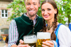 Couple wearing Tracht posing with glasses in beer garden Stock Photography