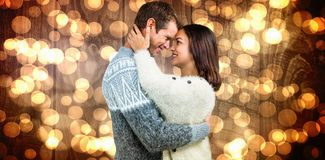 Composite image of couple wearing warm clothing embracing Stock Photos