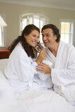 Couple wearing white bath robes on bed, both holding telephone receiver, smiling Stock Image