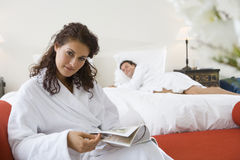 Couple wearing white bath robes in bedroom, portrait of woman sitting with magazine in foreground. Couple wearing white bath robes in bedroom, portrait of women Stock Images