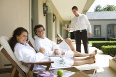 Couple wearing white bath robes on deck chairs, man smiling at woman holding magazine, waiter standing in background Royalty Free Stock Images