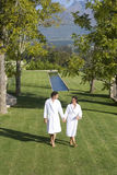 Couple wearing white robes, holding hands whilst walking in garden, elevated view Stock Photos
