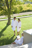 Couple wearing white robes, holding hands whilst walking in garden by woman, elevated view Stock Image