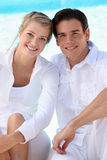 Couple wearing white. Young couple wearing white with a blue sky background Stock Photo