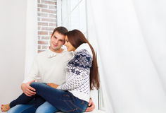 Couple wearing winter clothes at home relaxing Stock Photo