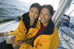 Couple wearing yellow anoraks on yacht Stock Photo