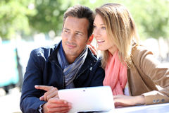 Couple websurfing on tablet outdoors Royalty Free Stock Photography