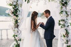 Couple in wedding arch exchange rings with lake on background, the bride with long beautiful hairs and groom in black. Suit look at each other in wedding day Stock Photos