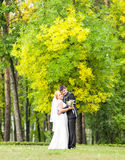Couple in wedding attire with a bouquet of flowers, bride and groom outdoors Stock Photography