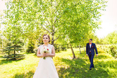 Couple in wedding attire with a bouquet of flowers and greenery is in the hands against the backdrop of the garden, the Royalty Free Stock Photo