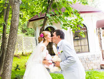 Couple in wedding attire with a bouquet of flowers and greenery is in the hands, the bride and groom kissing Stock Photography