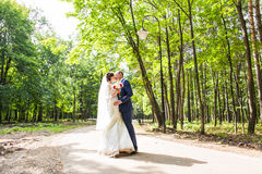 Couple in wedding attire with  bouquet of flowers outdoors,  bride and groom Royalty Free Stock Image
