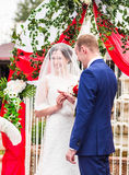 Couple in wedding attire exchange rings   with arch on background. Couple in wedding attire exchange rings with a bouquet of flowers and greenery in the garden Stock Image