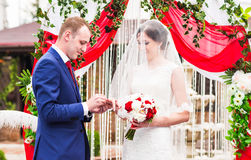 Couple in wedding attire exchange rings   with arch on background. Couple in wedding attire exchange rings with a bouquet of flowers and greenery in the garden Stock Photo
