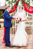 Couple in wedding attire exchange rings   with arch on background. Couple in wedding attire exchange rings with a bouquet of flowers and greenery in the garden Royalty Free Stock Photo