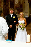 Couple at wedding ceremony. Couple stood in church during wedding ceremony, rear view of priest in foreground Stock Photos