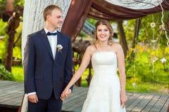Couple on wedding ceremony under arch. Smiling couple during wedding ceremony under decorative arch Stock Image