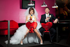 The couple in the wedding day sitting in the red chairs with the heart in the billiard room and drink cocktail. The couple in the wedding day sitting in the red Royalty Free Stock Photo