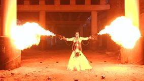 A couple in wedding dresses and with makeup for Halloween perform a fire show. A couple in wedding dresses and with skull-like makeup perform a fire show in an stock footage