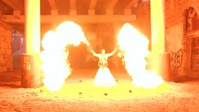 Couple with a terrible makeup for Halloween perform fire show. Halloween. A couple in wedding dresses and with skull-like makeup perform a fire show in an stock footage