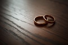 Couple of wedding rings on wooden table stock images