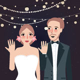 Couple at wedding show their ring party at night light string hanging.  Royalty Free Stock Photos
