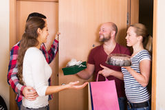 Couple welcomes happy friends Stock Photo