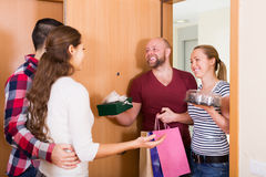 Couple welcomes smiling friends Stock Photos