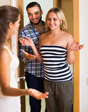 Couple welcoming friend at doorway Stock Photography