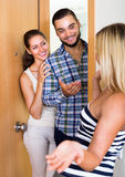 Couple welcoming friend at doorway Royalty Free Stock Photos