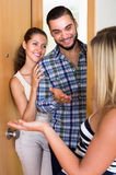 Couple welcoming friend at doorway Stock Image