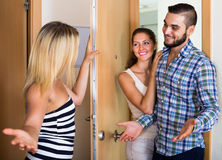 Couple welcoming friend at doorway Stock Photos
