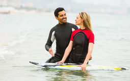 Couple in wetsuits with surf boards Stock Images