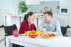 Couple on wheelchair eating common meal indoors. Couple on a wheelchair eating the common meal indoors Stock Images