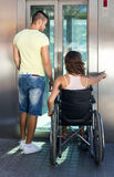Couple with wheelchair in elevator Stock Image