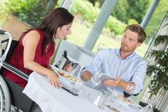 Couple wheelchair having lunch stock image