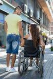 Couple at wheelchair walk through city Stock Photo