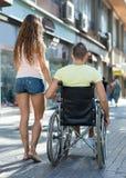 Couple at wheelchair walk through city streets Stock Photos