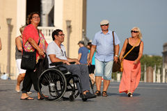 Couple with wheelchair and walking couple. A woman brings her disabled husband around (Vatican city - Rome - Italy) / another couple strolling carefree / concept Royalty Free Stock Photo