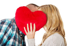 Couple whispering behind the pillow Stock Images