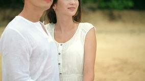 Couple in white clothes on a tropical beach. Against the background of a ship and palm trees stock footage