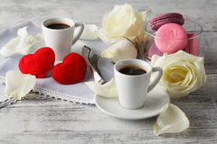 Couple white cups with decoration by red hearts on wooden table. Stock Photos