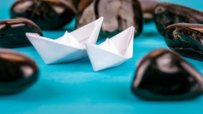 Couple of White Paper Ships between Abstract Black Rock Stones on Blue Background Royalty Free Stock Photos