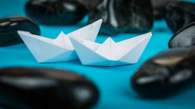 Couple of White Paper Ships between Abstract Black Rock Stones on Blue Background Stock Images