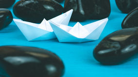 Couple of White Paper Ships between Abstract Black Rock Stones on Blue Background. Vintage Look Royalty Free Stock Photos