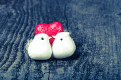 Couple of white pigeons with shiny red heart on old wooden backg Royalty Free Stock Photo