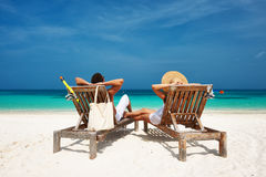 Couple in white relax on a beach at Maldives Stock Photos